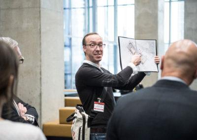 De gids illustreert zijn verhaal met een beeldboek.