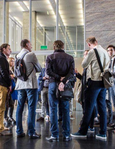 De gids ontvangt de deelnemers in de lobby van het gebouw De Rotterdam.
